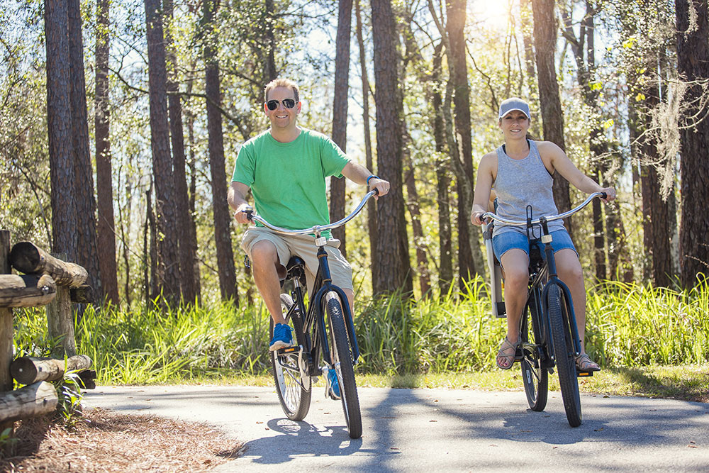 Happy attractive couple on a bike ride together outdoors on a bicycle path in the woods. Bike rental photo